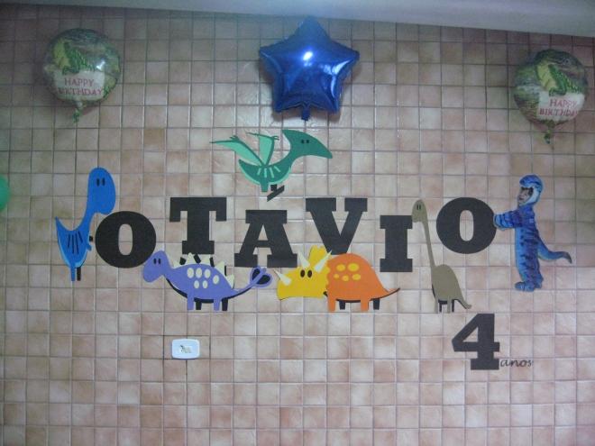 """Para enfeitar a parede, dinos carregando as letras do nome do meu filho. E olha ele ali fantasiado de dino empurrando a letra """"o"""""""